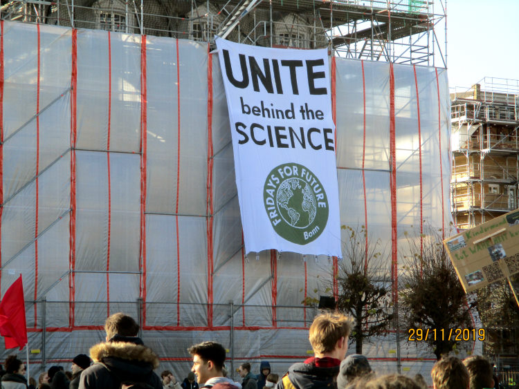 Fridays for Future Demo in Bonn. Banner am Baugerüst mit der Aufschrift: Unite behind the science.